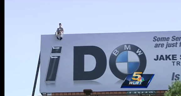 mannequin on top of billboard sign