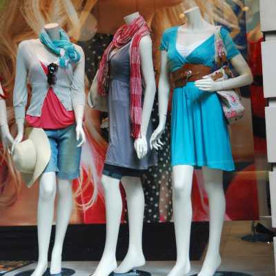 dressed fiberglass female mannequins in window of clothing store